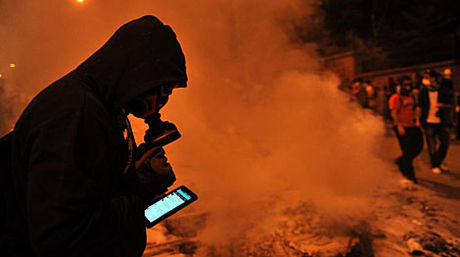 Jóvenes marchando con una bandera en la mano y un celular en la otra para no perder registro