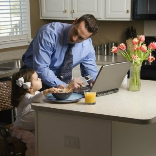 caucasian-father-in-suit-using-laptop-computer-with-daughter-eating-breakfast-in-kitchen