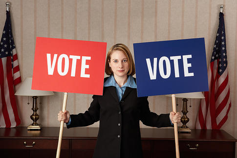 woman holding vote posters