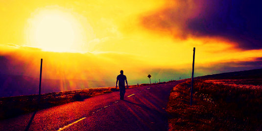 man walking on the road sunset